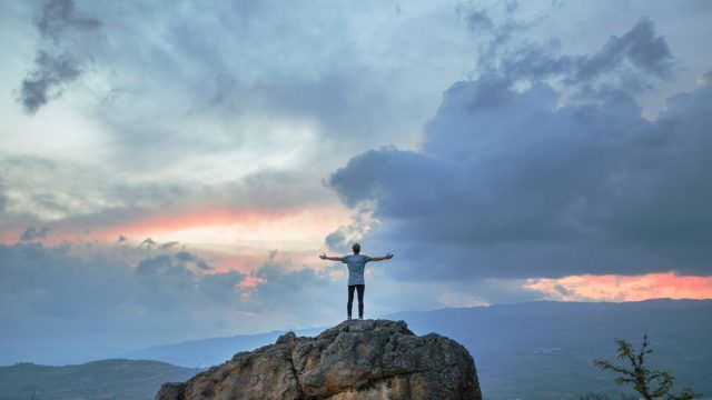 Man on rock with arms outstretched