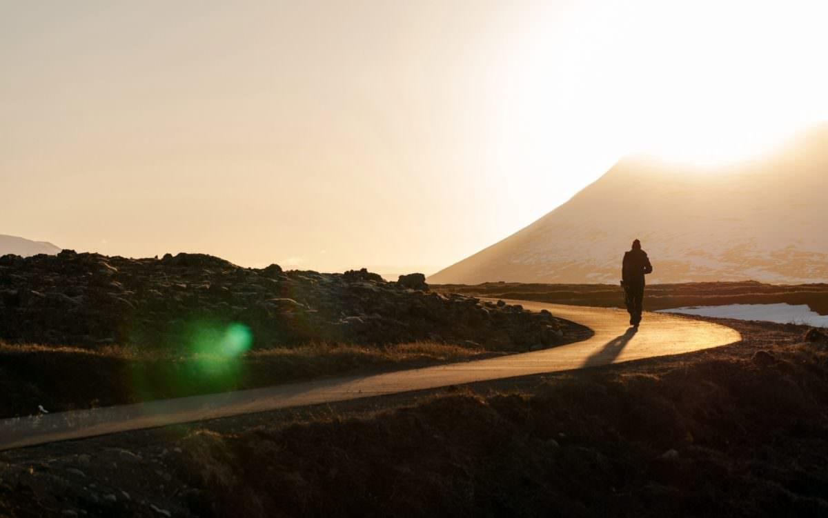 Person walking along road into the horizon