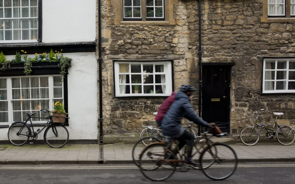Photo of two friends biking together on a street