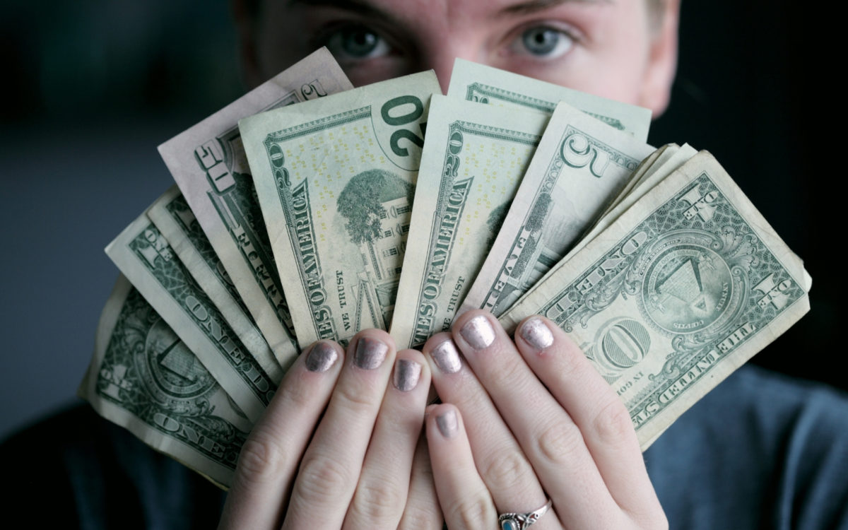 Woman holds money greedily