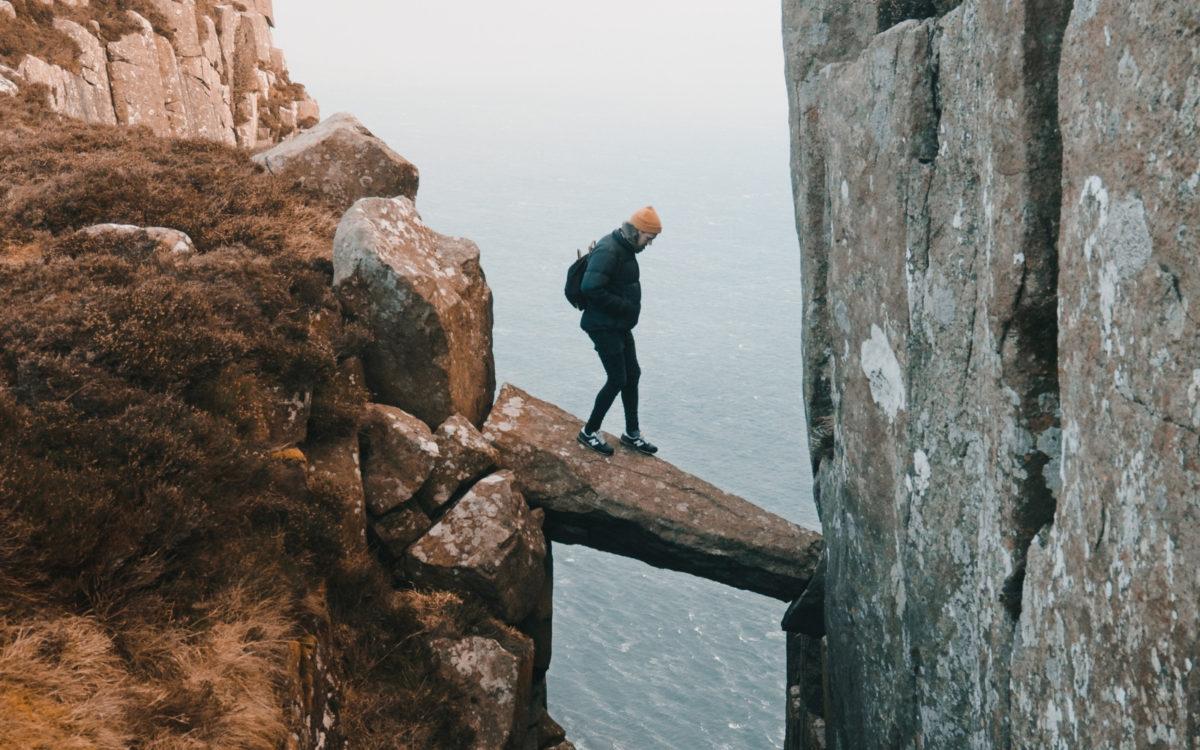 Climber crossing precarious rock bridge